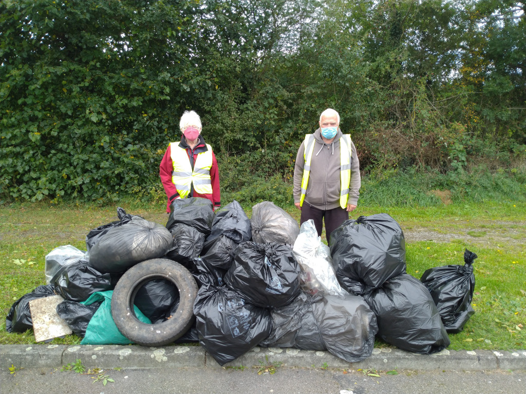 Phot of volunteers standing behind a pile of litter